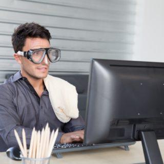 Hitze im Büro: Mitarbeiter schwitzt vor dem Rechner